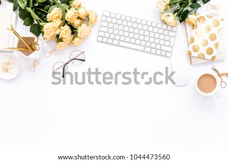 Female workspace with computer, roses flowers bouquet, golden accessories, diary, laptop, glasses on white background. Flat lay women\'s office desk. Top view feminine background.