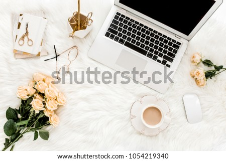 Female workspace with laptop, roses flowers bouquet, golden accessories, notebook, glasses. Flat lay women's office desk. Top view feminine background. #1054219340