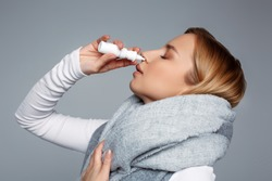 Female wrapped in scarf using nasal spray medicine for runny nose . Seasonal health issues. Allergic chronic rhinitis, common cold, sinusitis concept. First symptoms of flu, virus or disease