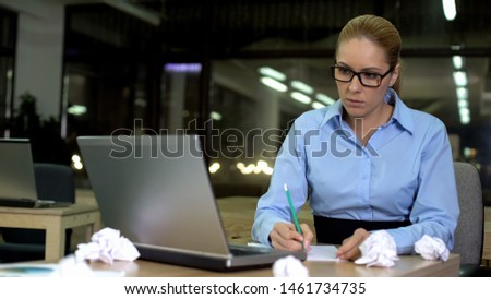 Female writing ideas for presentation on papers at night in office, lack of idea