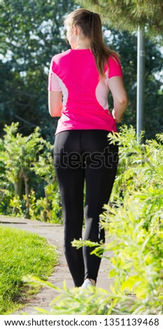 Female 20-30 years old is jogging back in pink T-shirt in the park.