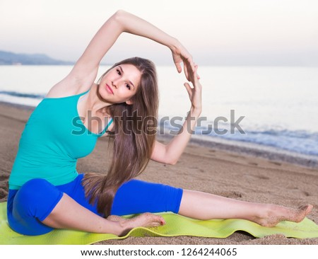 Female 20-25 years old is practicing stretching  in white T-shirt on the beach near sea.