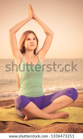 Female 20-25 years old is sitting and practicing meditation in blue T-shirt on the beach.