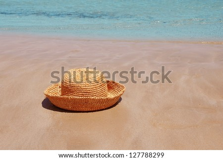 female yellow hat on beach by blue sea - stock photo