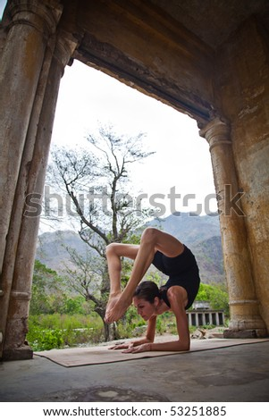 Female yoga teacher executing postures (asanas) at an old hotel in Rishikesh, India.