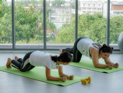female yoga trainner teaching fat overweight woman to practice fitness yoga exercise for relax and healthy concentration on the mat in yoga studio healthclub