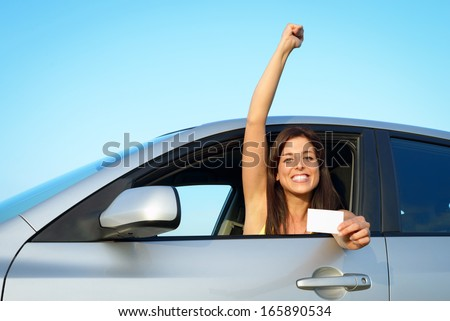 Female young driver in her car after passing the driving license test. Successful woman showing blank card in vehicle.