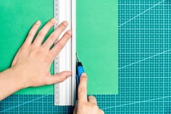 Female young hands cutting a green sheet of paper with a cutter and a metal ruler on a cutting board. Flat lay image with copy space.