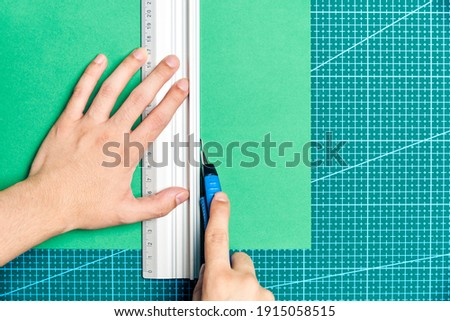 Female young hands cutting a green sheet of paper with a cutter and a metal ruler on a cutting board. Flat lay image with copy space. Сток-фото ©