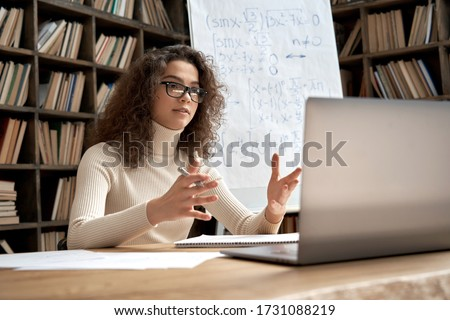 Female young hispanic school math teacher, college tutor coach looking at webcam and talking in classroom giving virtual teaching remote class online lesson by zoom conference call on laptop computer.