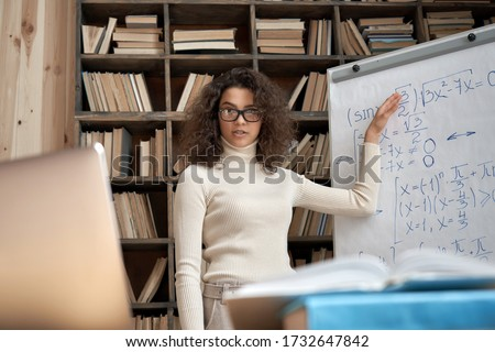 Female young hispanic university teacher, college tutor explaining math giving remote school class online lesson teaching looking at laptop in classroom by elearning webcam video conference zoom call.