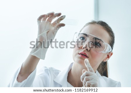 Female young scientist with microscope looking biology test slide on white background in Medical laboratory