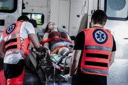 Female young victim of the accident lies on a stretcher in an ambulance