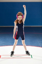 Female youth wrestler with her arm raised in victory
