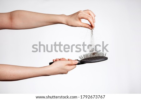 Females hands clean the comb from fallen hair. Close up. White background. Concept of hair loss, baldness and hair care