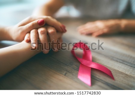 Females hands. Top view, close up. Pink ribbon like a symbol of Breast Cancer Awareness. #1517742830