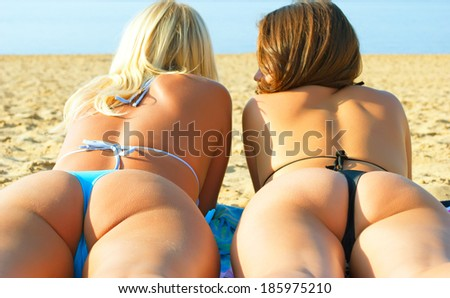 Females in thongs on the beach.