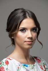 Feminine beautiful young woman with bun hairdo looking at camera over gray studio background.