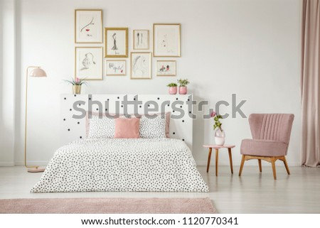 Feminine bedroom interior with white walls, polka dot bedding, pink elements and fashion drawings gallery in golden frames