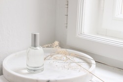 Feminine cosmetic still life scene. Glass bottle, flacon with perfume or eau de toilette and dry grass on white marble tray near window. Selective focus, blurred window sill background.