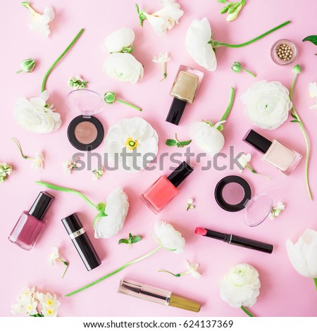 Feminine desk with cosmetics, lipstick, nail polish, eye shadows and white flowers on pink background. Flat lay, top view. Beauty background #624137369