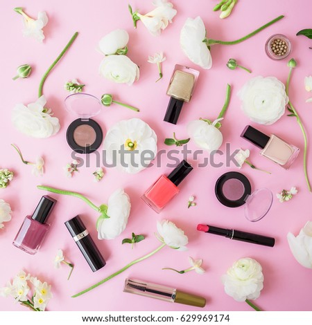 Feminine desk with woman cosmetics and white flowers on pink background. Flat lay, top view. Beauty background for woman #629969174