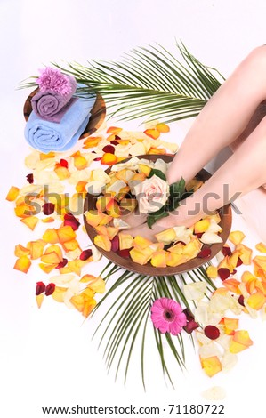 Feminine feet in foot spa bowl with flowers, petals and towels
