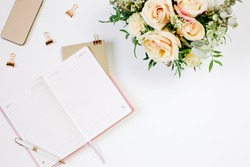 Feminine flat lay of pink opened notebook, bouquet and office supplies with copy space millennial pink color paper background minimal style. Template for feminine blog social media. Mood and blogging