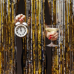 Feminine hand holds clock showing almost midnight and a glass of champagne on the background of shiny metallic curtain. New Year's Eve, festive party concept.