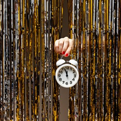 Feminine hand holds clock showing almost midnight on the background of shiny metallic curtain. New Year party concept.