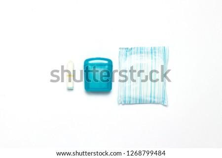 Feminine hygiene tampons, box for shipping and storage and sanitary pad on a white background. Concept of feminine hygiene during menstruation, choice between pads and tampons. Flat lay, top view. #1268799484