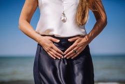 Feminine power. Woman holding hands on womb. Self care and self love. Feminine energy. Female practises.Woman on a beach.