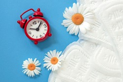 feminine sanitary pads, white chamomile flowers, alarm clock on blue background, concept of feminine health and hygiene, menopause, periodic menstruation