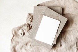 Feminine stationery, desktop mock-up scene. Blank greeting card, craft envelope, sea shells and old books on beige linen tablecloth background. Flat lay, top view. Summer rustic composition