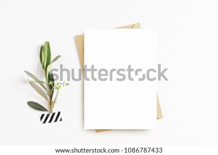 Feminine stationery, desktop mock-up scene. Blank greeting card, craft envelope, washi tape and with olive branch.White table background. Flat lay, top view.