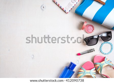 Feminine summer background. Set of summer women\'s accessories: sunglasses, shoes, passport, blue striped bag, pink lipstick, blush, perfume on white wood background. Vacation/travel. Space for text