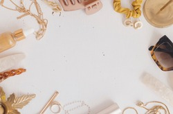 Feminine summer essentials flat lay, space for text. Gold jewellery, sunglasses, hair clips, barrettes, cosmetics on white table with vintage candles. Modern boho accessories
