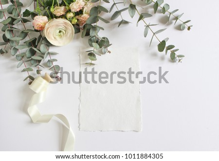 Feminine wedding, birthday desktop mock-up scene. Blank paper greeting card and bouquet of eucalyptus branches, pink roses and Persian buttercup flowers. White table background. Flat lay, top  view.