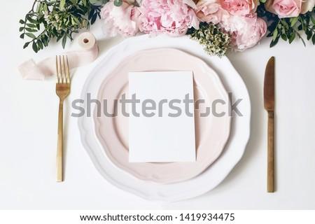 Feminine wedding, birthday desktop mock-up scene. Porcelain plates, blank paper greeting, menu card, ribbon, golden cutlery, leaves,roses, peony flowers. White table background. Flat lay, top view