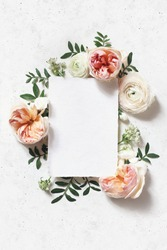 Feminine wedding, birthday mock-up scene. Blank paper greeting card. Floral frame of blush pink English roses, ranunculus flowers and lentisk leaves. Concrete table background. Flat lay, top view.