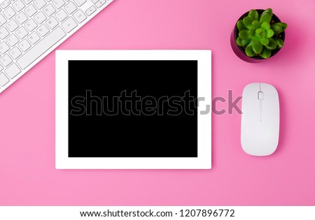 Feminine workplace concept. Items on bright pink background, top view. a tablet on a pink table. Flat lay. Copy space.  White tablet on the pink table with succulent, key board and mouse.