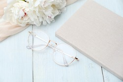 Feminine workspace with paper notebook, glasses, beige cloth on blue wooden background. Flat lay, top view. Beauty blogger workplace