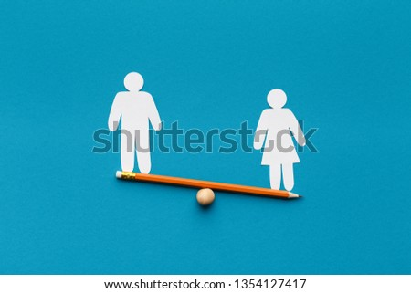 Feminism, women fight for equal rights. Female figure outweigh male on seesaw, blue background