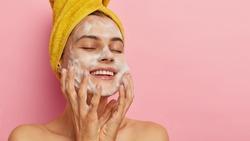 Feminity and hygiene concept. Young delighted female washes face with soap, smiles happily, closes eyes from satisfaction, cleans skin, poses against pink background with blank space for your promo