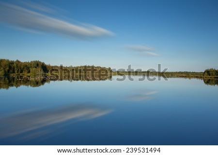 Fen landscape with light blue sky and clouds reflected in water