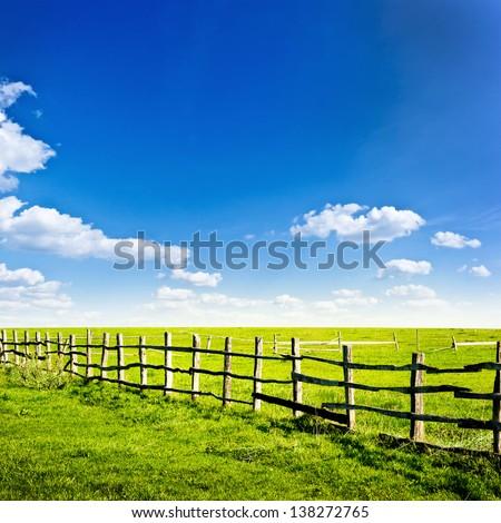 Fence in the green field under blue cloud sky. Beautiful landscape #138272765