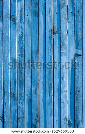 Fence made of narrow old blue planks. Boards with knots and slots are arranged vertically. Vertical frame.