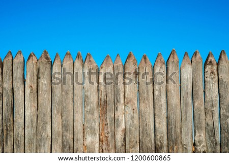 Fence made of sharp wooden stakes against the blue sky. Wooden fence vertical logs pointed against the sky protection against invaders and wild animals