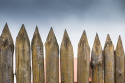 Fence made of sharp wooden stakes against the grey cloudy sky.