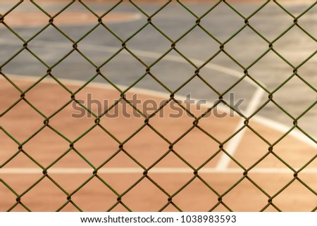 fence metal mesh with blurred basketball court background #1038983593